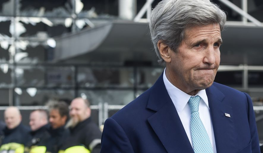 Blown out windows are seen behind U.S. Secretary of State John Kerry as he visits Brussels Airport in Brussels, Belgium, Friday, March 25, 2016. Kerry is in Brussels to pay respect to victims of terrorist attacks that left a number dead earlier this week. (Frederic Sierakowski/pool photo via AP)
