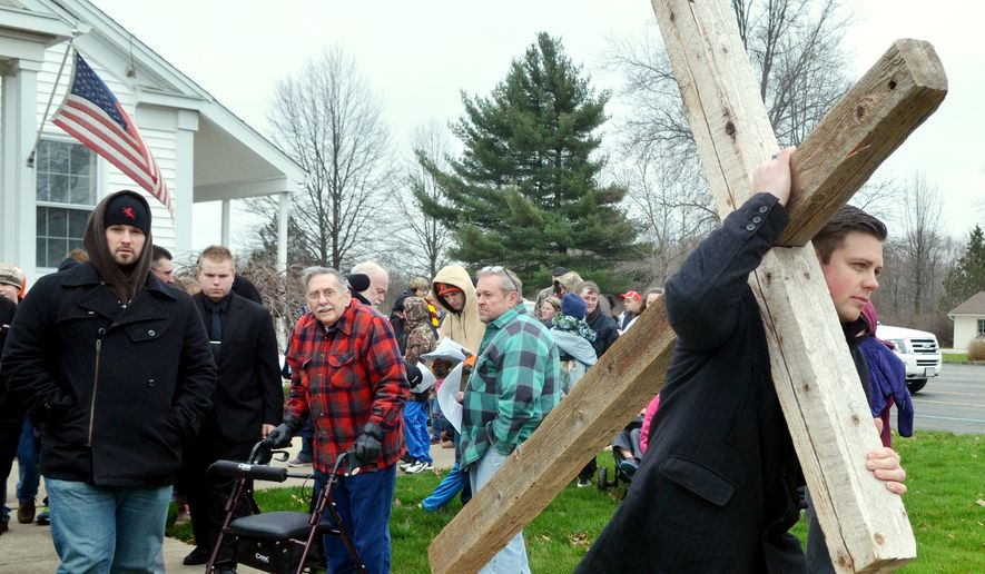 Skyler O'Donnell, of Pymatuning Community Church, picks up a cross during the Pymatuning Valley Ministerial Association Cross Walk in the village of Andover, Ohio, Friday, March 25, 2016. (Warren Dillaway/The Star-Beacon via AP) ** FILE **