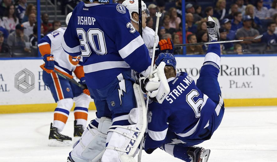 Tampa Bay Lightning's Anton Stralman, of Sweden, falls in front of goalie Ben Bishop during the first period of an NHL hockey game against the New York Islanders on Friday, March 25, 2016, in Tampa, Fla. Stralman was helped off the ice and did not immediately return. (AP Photo/Mike Carlson)