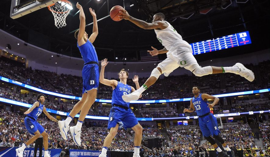 Oregon's Elgin Cook passes the ball as Duke forward Chase Jeter defends during the first half of an NCAA college basketball game in the regional semifinals of the NCAA Tournament, Thursday, March 24, 2016, in Anaheim, Calif. (AP Photo/Mark J. Terrill)