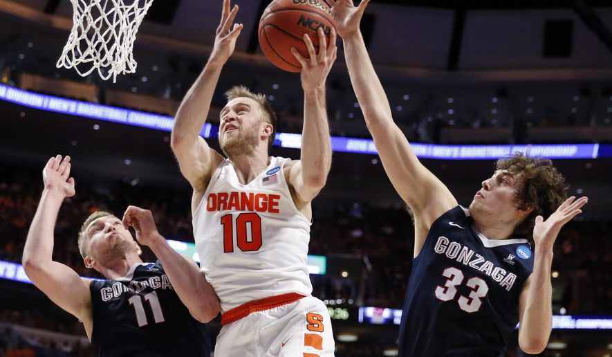 Gonzaga's Kyle Wiltjer (33) blocks a shot by Syracuse's Trevor Cooney (10) as Cooley shoots against Gonzaga's Domantas Sabonis (11) during the first half of a college basketball game in the regional semifinals of the NCAA Tournament, Friday, March 25, 2016, in Chicago. (AP Photo/Charles Rex Arbogast)