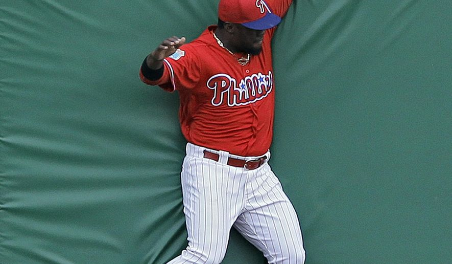 Philadelphia Phillies center fielder Odubel Herrera crashes into the wall after making the catch on a fly out by Toronto Blue Jays' Kevin Pillar during the first inning of a spring training baseball game Friday, March 25, 2016, in Clearwater, Fla. (AP Photo/Chris O'Meara)