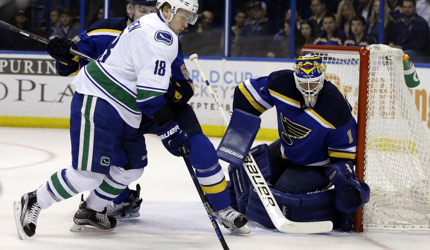 Vancouver Canucks' Jake Virtanen, left, controls the puck as St. Louis Blues goalie Brian Elliott defends during the first period of an NHL hockey game Friday, March 25, 2016, in St. Louis. (AP Photo/Jeff Roberson)
