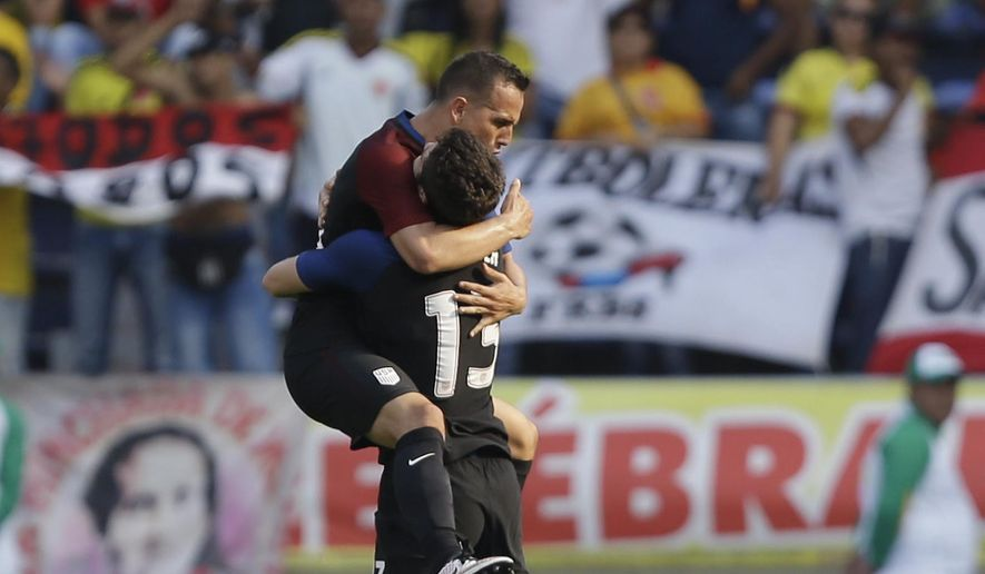 United States' Luis Gil, left, is embraced by teammate Matt Polster after scoring his side's first goal against Colombia  during a U-23 first leg soccer match qualifier for the 2016 Rio Olympics at the Roberto Melendez Stadium in Barranquilla, Colombia, Friday, March 25, 2016. (AP Photo/Fernando Vergara)