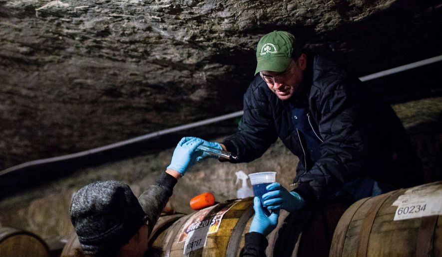 Jason Heystek, Founders Brewing Company's Vice President of Planning, Packaging, Inventory & Logistics, passes a cup of beer and a baster used to remove the craft beer from a barrel which the beer has been aging in since 2015 in a mine 85 feet underground at Michigan Natural Storage on Feb. 26, 2016 in Grand Rapids, Mich.  (Andraya Croft/Detroit Free Press via AP)  DETROIT NEWS OUT; TV OUT; MAGS OUT; NO SALES; MANDATORY CREDIT DETROIT FREE PRESS