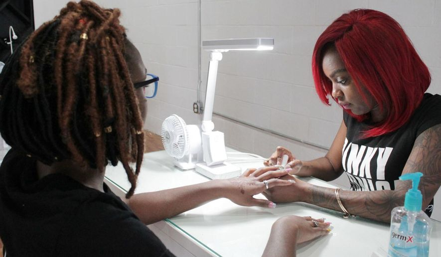 ADVANCE FOR USE SATURDAY, MARCH 26, 2016, AND THEREAFTER- In this undated photo, Jasmine Baccus, left, gets her nail polished by her sister and nail artist Jarrel Baccus at Pinky Promise Nail Studio in Quinby, S.C. At 24 years old, Jarrel Baccus is an established business owner with a clientele that goes beyond the Pee Dee area. (Shamira McCray/Savannah Morning News via AP) THE EXAMINER.COM OUT; SFEXAMINER.COM OUT; WASHINGTONEXAMINER.COM OUT; MANDATORY CREDIT