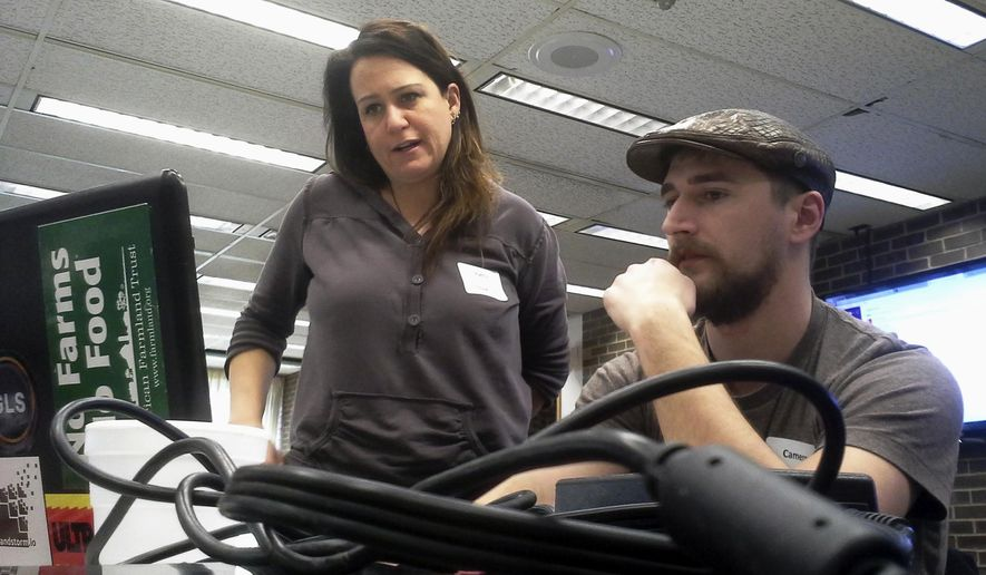 In this March 5, 2016 photo, Patty Ruback, 41, left, and Cameron Willis, 28, both of DeKalb, Ill. discuss the setup of a website that would connect producers of locally grown food, among other products, and consumers during CodeAcross, an annual event promoted by the organization Code for America in which people gather to use code to solve real-world problems. (Keith Hernandez/Daily Chronicle via AP) CHICAGO TRIBUNE OUT, MANDATORY CREDIT