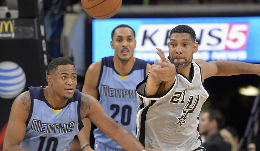 San Antonio Spurs forward Tim Duncan (21) pokes the ball away from Memphis Grizzlies forward Jarell Martin (10) as Grizzlies' Ryan Hollins looks on during the first half of an NBA basketball game, Friday, March 25, 2016, in San Antonio. (AP Photo/Darren Abate)