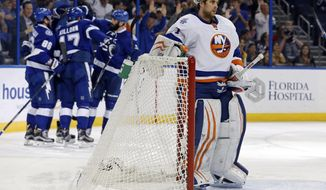 New York Islanders goalie Thomas Greiss, of Germany, reacts as Tampa Bay Lightning players celebrate a goal during the second period of an NHL hockey game Friday, March 25, 2016, in Tampa, Fla. (AP Photo/Mike Carlson)