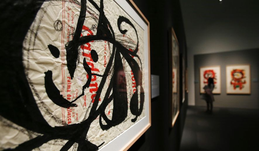 "A woman watches paintings during the press preview of the exhibition "" Joan Miro - La forza della materia "" (The Force of Matter) , a selection of works realized between 1931 and 1981 from the Catalan artist, at the Mudec museum in Milan, Italy, Thursday, March 24, 2016. (AP Photo/Antonio Calanni)"