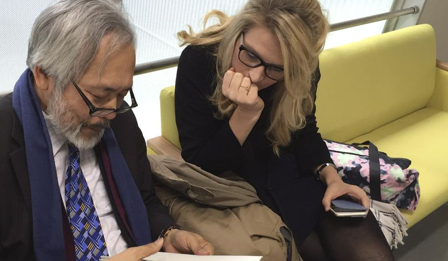 In this photo provided by Damien McKeon, Australian animal welfare activist Sarah Lucas talks with her lawyer Takashi Takano at Wakayama District Court in Wakayama, western Japan, Friday, March 25, 2016. The court ruled Friday that an aquarium had no right to bar Lucas, who wanted to check on a baby albino dolphin in captivity. The court awarded Lucas 110,000 yen ($970) in damages, a court official said, on customary condition of anonymity. Lucas, the head of Australia for Dolphins, called the verdict a victory in the fight to stop dolphin killings. She expressed concern for the albino dolphin, saying it was in a tiny crowded tank of chlorinated water, being bullied by other dolphins. (Damien McKeon via AP)