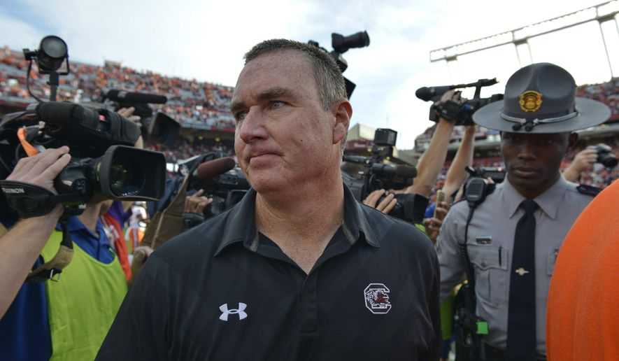 FILE -In this Saturday, Nov. 28, 2015 file photo, South Carolina interim head coach Shawn Elliott leaves the field after an NCAA college football game against Clemson, in Columbia, S.C.  Elliott wasn't sure what he'd do next after his half-season stint as South Carolina's interim coach last fall. New leader Will Muschamp made sure Elliott didn't have much choice in keeping him as offensive line coach. The familiar face has made the Gamecocks transition to a new coaching staff smoother this offseason. (AP Photo/Richard Shiro, File)