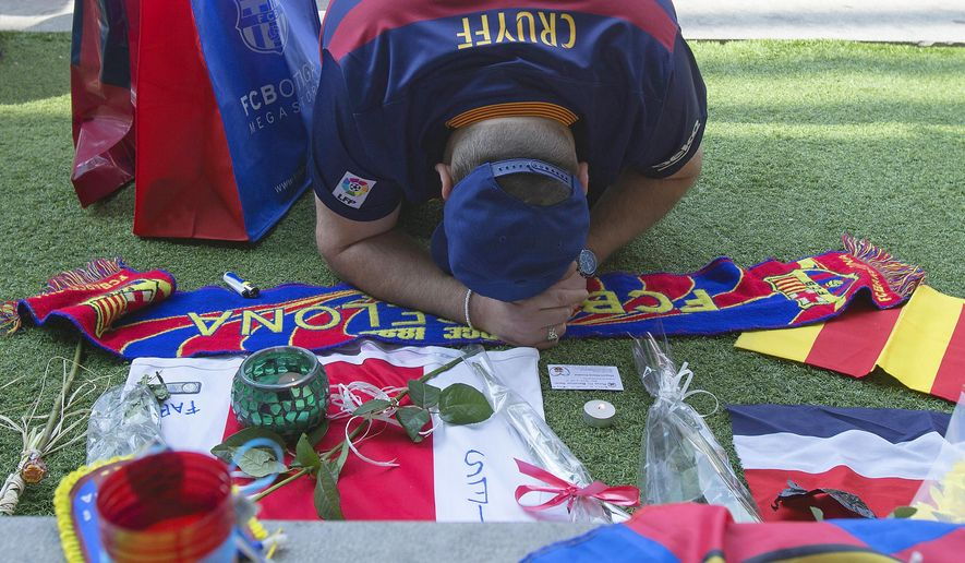"A FC Barcelona supporter offers his respects to the late Dutch soccer great Johan Cruyff at the Camp Nou stadium in Barcelona, Spain, Friday, March 25, 2016. Dutch soccer great Johan Cruyff, who revolutionized the game as the personification of ""Total Football,"" has died. He was 68.  (AP Photo/Fernando Viros)"