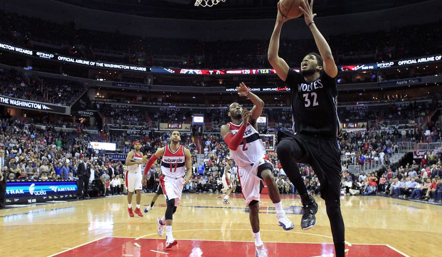 Minnesota Timberwolves center Karl-Anthony Towns (32) shoots in front of Washington Wizards guard John Wall (2) late in the second overtime period of an NBA basketball game Friday, March 25, 2016, in Washington. The Timberwolves won 132-129. (AP Photo/Alex Brandon)