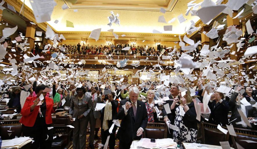 FILE - In this March 25, 2016 file photo, representatives throw papers up in the air at the conclusion of the final day of the Georgia General Assembly at the capitol in Atlanta. State lawmakers finished their annual legislative session on Thursday. The Associated Press takes a look at the what happened and what issues remain on the table for the state moving forward.  (AP Photo/Jason Getz)
