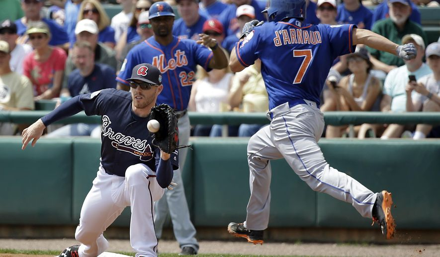 New York Mets' Travis d'Arnaud (7) is unable to beat the throw to Atlanta Braves first baseman Freddie Freeman, left, and is forced out in the first inning of a spring training baseball game, Saturday, March 26, 2016, in Kissimmee, Fla. (AP Photo/John Raoux)