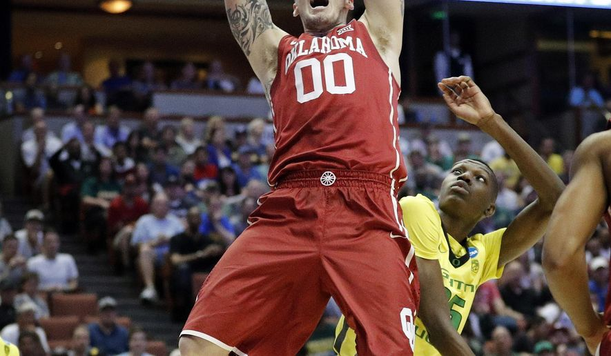 Oklahoma forward Ryan Spangler dunks over Oregon forward Chris Boucher during the first half of an NCAA college basketball game in the regional finals of the NCAA Tournament, Saturday, March 26, 2016, in Anaheim, Calif. (AP Photo/Gregory Bull)