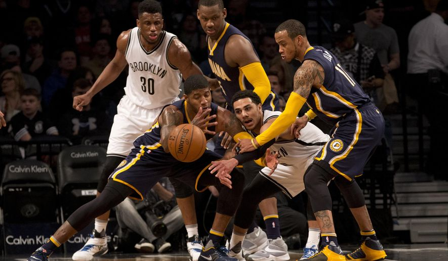 Indiana Pacers forward Paul George, front left, and Brooklyn Nets guard Shane Larkin, front right, fight for the ball during the first half of an NBA basketball game, Saturday, March 26, 2016, at New York. (AP Photo/Mary Altaffer)