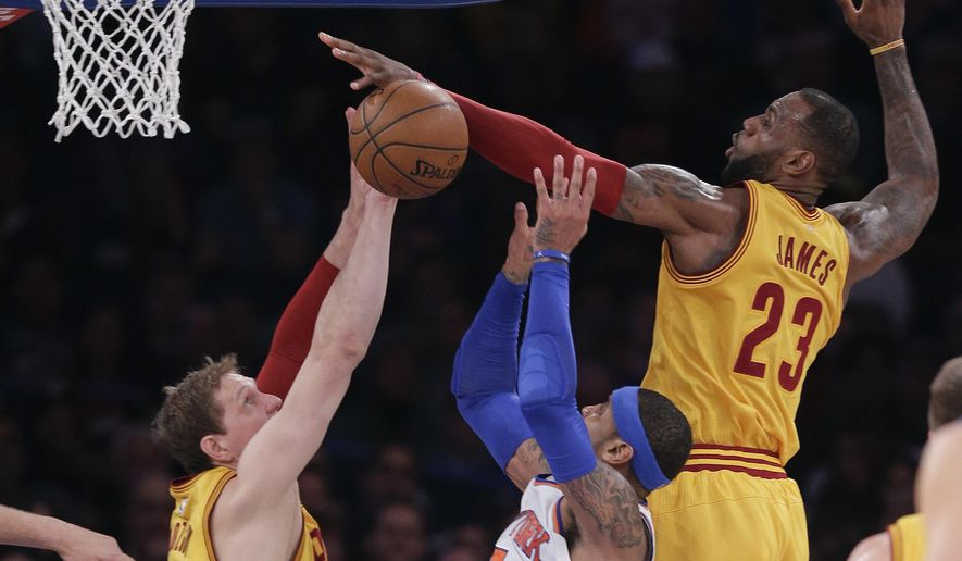 Cleveland Cavaliers forward LeBron James (23) blocks a shot by New York Knicks forward Carmelo Anthony (7) as Cleveland Cavaliers center Timofey Mozgov (20) helps defend during the second quarter of an NBA basketball game, Saturday, March 26, 2016, in New York. (AP Photo/Julie Jacobson)