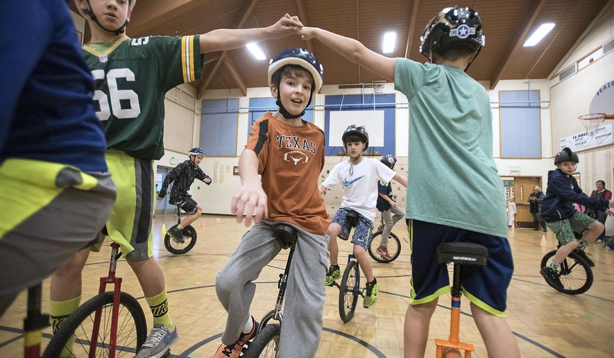 ADVANCE FOR USE SATURDAY, MARCH 26 - In this photo taken March 9, 2016, Isaiah Thomas, center, and fellow sixth graders fill the gymnasium floor while riding unicycles during rehearsal for the circus arts performance at Prairie Elementary School in Yelm, Wash. Teacher LeighAnn Charlston began offering Circus Arts as part of physical education classes when she arrived at the school about 15 years ago.  (Tony Overman/The Olympian via AP) MANDATORY CREDIT