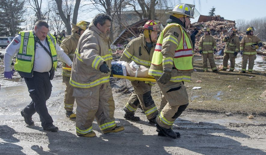 Rescue personnel carry one of the injured people to an ambulance after they were pulled from the rubble of a house that exploded in Richland Township, Mich., Friday, March 25, 2016. (Jeff Schrier/The Saginaw News - MLive.com via AP)