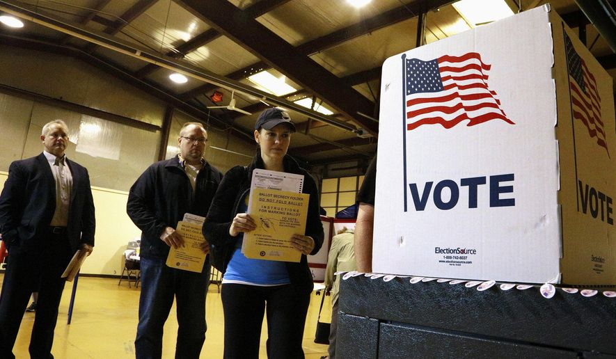 FILE - In this March 15, 2016 file photo, people line up to vote in the primary at a precinct in Bradfordton, Ill. Illinois lawmakers' budget fight is delaying parts of a new election law. That's leading officials to warn of long lines, fewer safeguards against voter fraud and other costly headaches in November. (AP Photo/Seth Perlman, File)