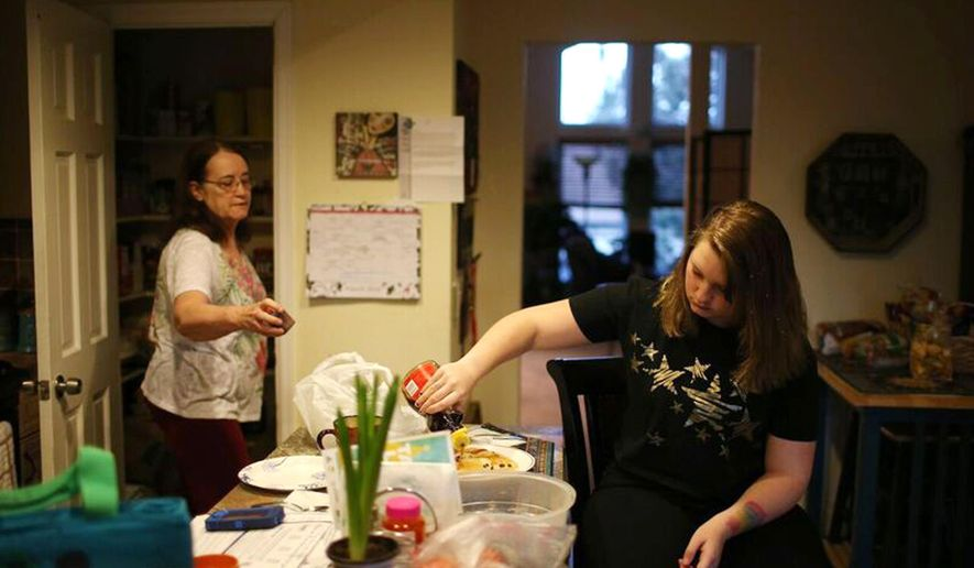HOLD FOR RELEASE UNTIL 12:01 A.M. MDT. THIS STORY MAY NOT BE PUBLISHED, BROADCAST OR POSTED ONLINE BEFORE 12:01 A.M. MDT.- In this Monday, March 14, 2016 photograph, Mickey Mauck, back, directs her 13-year-old granddaughter, Bree, as she helps in the preparation of a meal in their home in Aurora, Colo. Mauck has been caring for more than seven years for her granddaughter as a kinship provider, which involves relatives who have full-time responsibility for nurturing and protecting children who must be separated from their parents. (Gabriel Christus/Aurora Sentinel via AP)