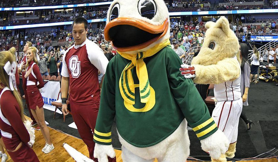 The Oklahoma mascot, right, greets the Oregon mascot before an NCAA college basketball game in the regional finals of the NCAA Tournament, Saturday, March 26, 2016, in Anaheim, Calif. (AP Photo/Mark J. Terrill)