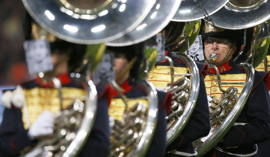 Members of a marching band have pictures  on their music books of deceased legendary soccer player Johan Cruyff prior to the international friendly soccer match between The Netherlands and France at the ArenA stadium in Amsterdam, Netherlands, Friday, March 25, 2016. (AP Photo/Peter Dejong)