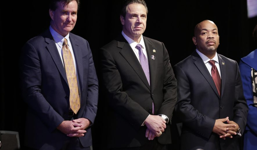 FILE--In this Jan. 13, 2016 file photo, New York Gov. Andrew Cuomo, center, stands with Senate Majority Leader John Flanagan, left, R-Smithtown, and Assembly Speaker Carl Heastie, D-Bronx, before delivering his State of the State address and executive budget proposal at the Empire State Plaza Convention Center in Albany, N.Y.  The biggest proposals of the year in Albany - a $15 minimum wage, paid family leave, higher taxes on millionaires, ethics reforms and a big jump in school spending _ will live or die this week as lawmakers piece together next year's state budget. (AP Photo/Mike Groll, File)
