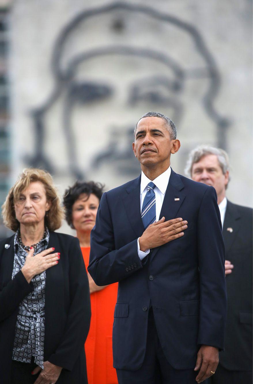 "Backdropped by a monument depicting Cuba's revolution hero Ernesto ""Che"" Guevara, U.S. President Barack Obama listens to the U.S. national anthem. (Associated Press)"
