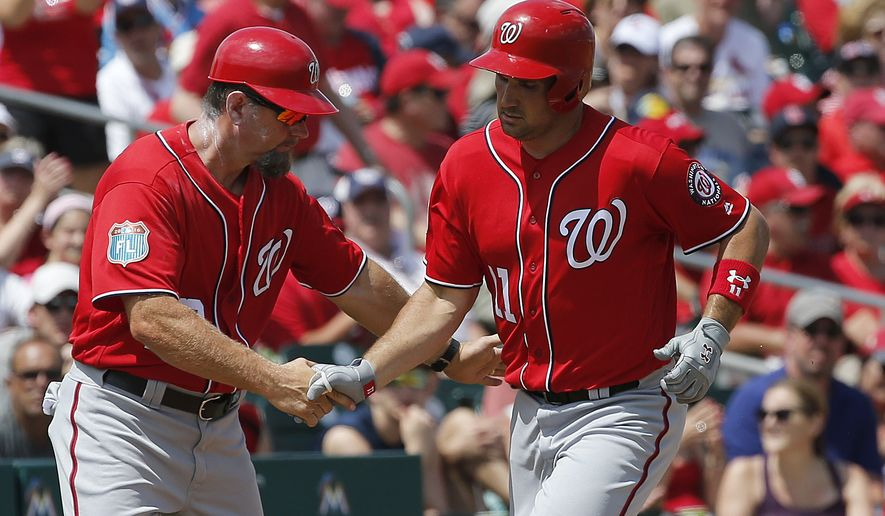 Washington Nationals third base coach Bob Henley, left, congratulates Ryan Zimmerman as he rounds third base after hitting a solo home run during the fourth inning of an exhibition spring training baseball game against the St. Louis Cardinals, Saturday, March 26, 2016, in Jupiter, Fla. (AP Photo/Brynn Anderson)