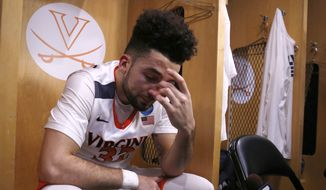 Virginia's London Perrantes (32) wipes his tears as he sits in the locker room after an NCAA college basketball game against Syracuse in the regional finals of the NCAA Tournament, Sunday, March 27, 2016, in Chicago. Syracuse won 68-62. (AP Photo/Charles Rex Arbogast)