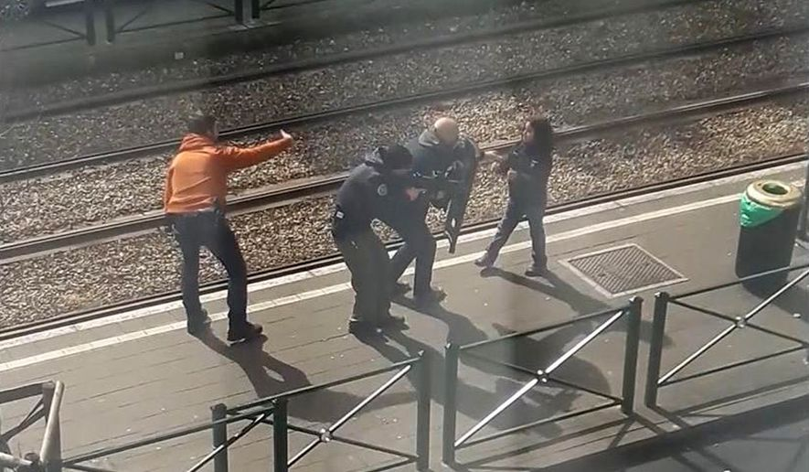 In this image taken from video filmed through a window, showing armed police as they coax a young girl away from a suspect who is laying on the ground at a tram stop in Brussels, Belgium, Friday March 25, 2016.   During an interview with The Associated Press on Sunday March 27, 2016, eyewitness Gracia Meta, describes how the unidentified young girl stood up and walked to the police and is then led away from the scene. (UGC via AP)