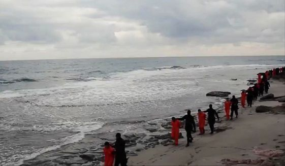 This image made from video released by militants in Libya claiming loyalty to the Islamic State group purportedly shows Egyptian Coptic Christians in orange jumpsuits being led along a beach, each accompanied by a masked militant. (Associated Press)