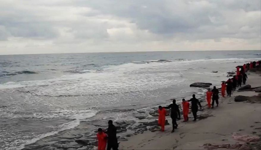 This image made from video released by militants in Libya claiming loyalty to the Islamic State group purportedly shows Egyptian Coptic Christians in orange jumpsuits being led along a beach, each accompanied by a masked militant. Libyan officials found a mass grave on Dec. 23, 2018, with 34 Ethiopian Christians slain by ISIS terrorists in 2015. (Associated Press) ** FILE **