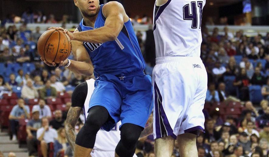 Dallas Mavericks guard Justin Anderson (1) passes under the basket around Sacramento Kings defender Kosta Koufos (41) during the first half of an NBA basketball game in Sacramento, Calif., Sunday, March. 27, 2016.(AP Photo/Steve Yeater)