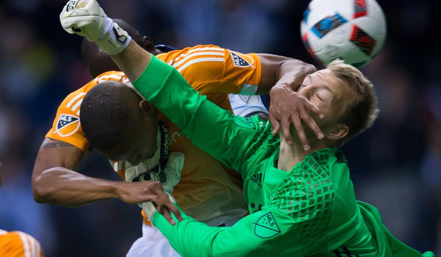 Houston Dynamo's Ricardo Clark, left, gets his hand on the face of teammate and goalkeeper Joe Willis as Willis tries to punch the ball away from Vancouver Whitecaps' Kekuta Manneh, rear, during the first half of an MLS soccer game in Vancouver, British Columbia, on Saturday, March 26, 2016. (Darryl Dyck/The Canadian Press via AP)