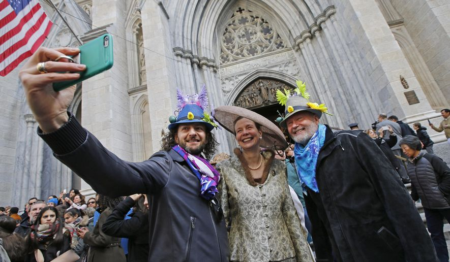 Massimiliano Musa, left, of Abruzzo, Italy, snaps a selfie of Cynthia Gable of Easton, Conn., center, along with Steven Tillman in front of St. Patrick's Cathedral during the annual Easter parade along Fifth Avenue, Sunday, March 27, 2016, in New York. (AP Photo/Kathy Willens)