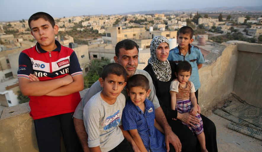 ADVANCE FOR THE WEEKEND OF MARCH 26-27 AND THEREAFTER - In a Sept. 15, 2016 photo, from left, Abdulbaset, 13, Obaidah, 12, father Ahmad Al Tybawi, Omar, 7, mother Ahlam Al Swedan, Abulhaq, 2, and Mohammad, 10, pose in Taiyyba, Jordan.  Four months after arriving from Jordan, the Syrian refugee family has faced hurdles amid a backlash sparked by terror attacks.   (Chris Kenning/The Courier-Journal via AP) NO SALES; MAGS OUT; NO ARCHIVE; MANDATORY CREDIT