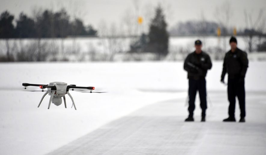 FILE - In this Jan. 15, 2015, file photo, Michigan State Police Sgt. Matt Rogers and Trooper Don Zinz bring the Aeryon SkyRanger in for a landing during a demonstration of the new Unmanned Aircraft System at the State Police training track in Dimondale, Mich. State transportation departments across the country are increasingly studying the use of unmanned aerial vehicles, better known as drones, for everything from inspecting bridges to helping clear car accidents. (Dale G. Young/Detroit News via AP, File) DETROIT FREE PRESS OUT; HUFFINGTON POST OUT; MANDATORY CREDIT