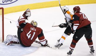 Arizona Coyotes' Mike Smith (41) makes a save on a shot by Philadelphia Flyers' Wayne Simmonds (17) as Coyotes' Zbynek Michalek (4), of the Czech Republic, defends on the play during the first period of an NHL hockey game Saturday, March 26, 2016, in Glendale, Ariz. (AP Photo/Ross D. Franklin)