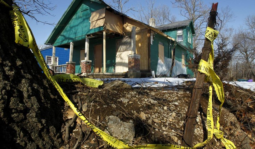 This Feb. 14, 2012 photo shows a boarded-up home in the Vineyard neighborhood of Kansas City. The city and the Land Bank of Kansas City have offered over a hundred derelict, generally unlivable structures for sale for $1 each to those willing to make them livable again within a year. Since launching the program in February 2016, the Land Bank has taken in more than 50 applications and fielded roughly 4,000 inquiries.  (Jill Toyoshiba/The Kansas City Star via AP) MANDATORY CREDIT