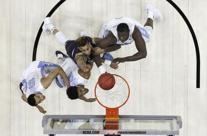 North Carolina's Marcus Paige, from left, Joel Berry II, Notre Dame's Zach Auguste and Joel James battle for a rebound during the first half of a regional final men's college basketball game in the NCAA Tournament, Sunday, March 27, 2016, in Philadelphia. (AP Photo/Chris Szagola)