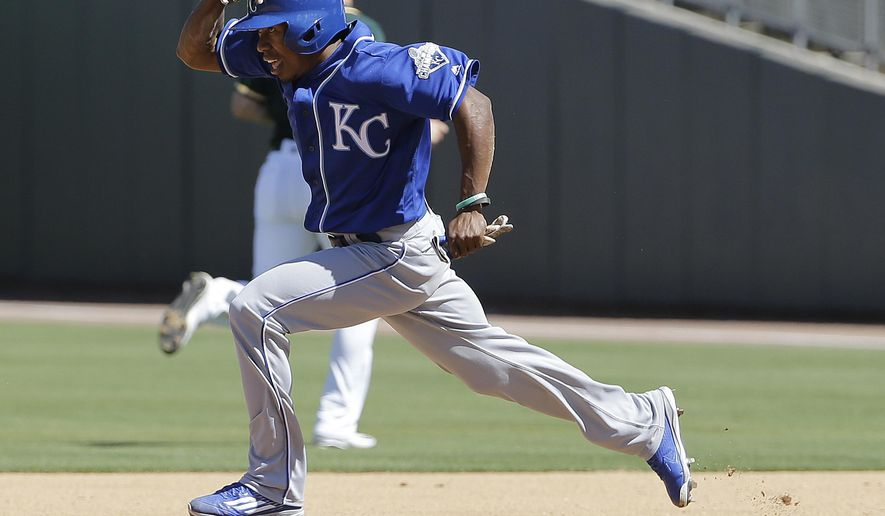Kansas City Royals' Terrance Gore runs to second base after a throwing error by Oakland Athletics pitcher Kendall Graveman during the fourth inning of a spring training baseball game in Mesa, Ariz., Sunday, March 27, 2016. (AP Photo/Jeff Chiu)