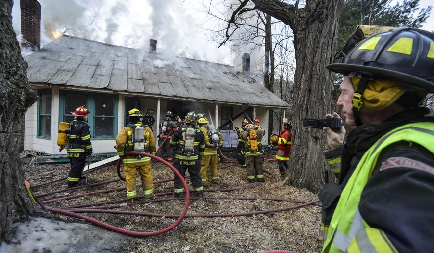 In this March 7, 2016 photo, Jacob White, a volunteer firefighter for Wilmington, Vt., records the scene during a fatal fire in Marlboro, Vt. The firefighter for the small Vermont town of Wilmington for more than 43 years is now fighting a rare form of cancer. (Kristopher Radder/The Brattleboro Reformer via AP) MANDATORY CREDIT