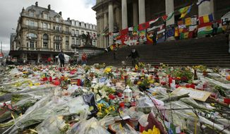 A general view of the tributes left for the victims of the recent bomb attacks in Brussels, following heavy rain in the Place de la Bourse in Brussels, Monday, March, 28, 2016. The Belgian health minister says four of those wounded in the suicide bombings last week have died in the hospital.(AP Photo/Alastair Grant)