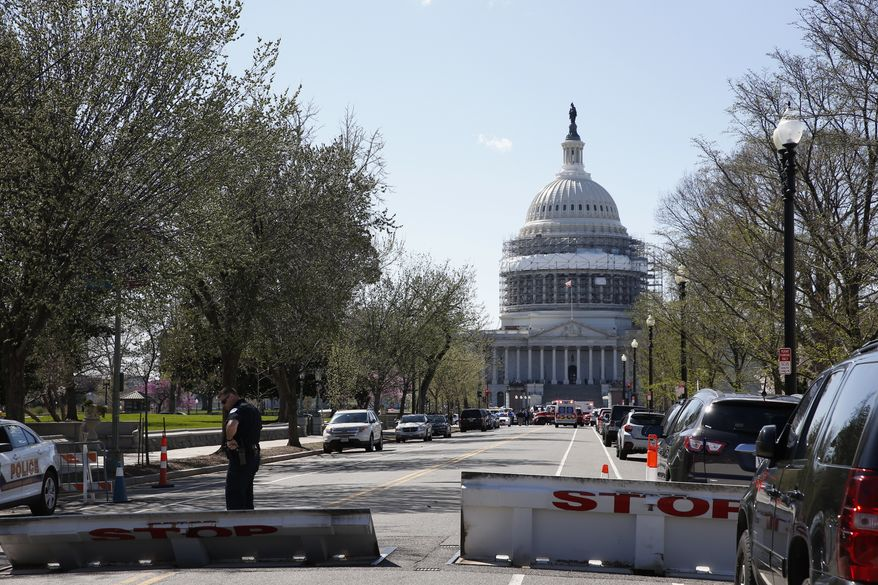 An officer stands guard on a street leading to Capitol Hill in Washington that is closed, Monday, March 28, 2018, after reports of gunfire at the Capitol Visitor Center complex. (AP Photo/Alex Brandon)