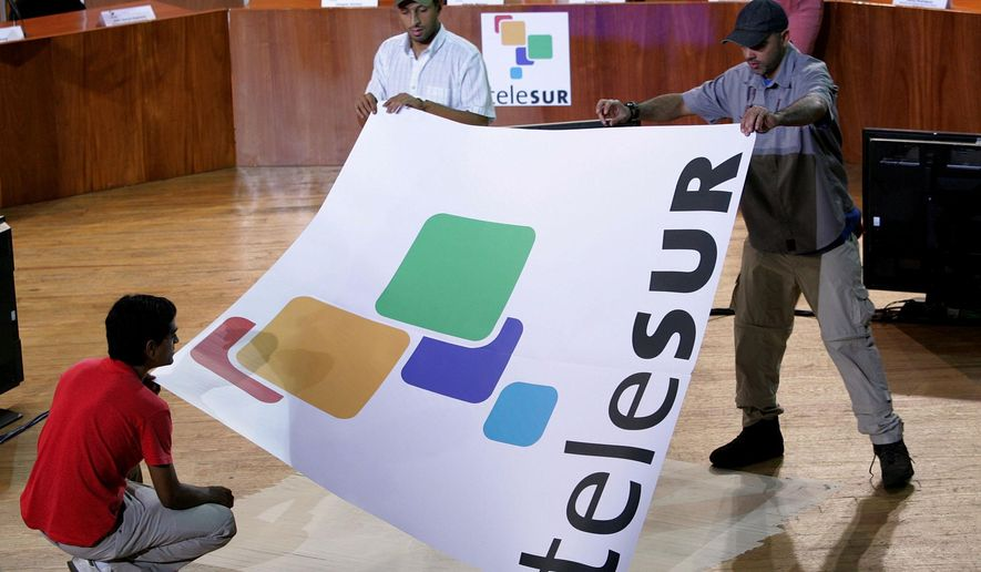 FILE - In this July 24, 2005, file photo, workers set up for the inauguration of Telesur in Caracas, Venezuela. Argentine Minister of Communication Hermann Lombardi announced Monday, March 28, 2016, that the country is pulling out of the Spanish-language television network started by the late Venezuelan President Hugo Chavez as a vehicle for promoting leftist politics in Latin America. (AP Photo/Leslie Mazoch,File)