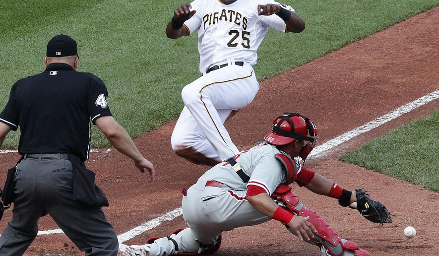 In this June 13, 2015 photo, Pittsburgh Pirates' Gregory Polanco (25) begins his slide as the ball bounces off the glove of Philadelphia Phillies catcher Carlos Ruiz during the first inning of a baseball game in Pittsburgh. Retired World Series-winning catcher Bob Boone has 60 video clips of home-plate collisions that resulted in injuries. None of those happened in the past two seasons since Major League Baseball instituted a new rule to prevent collisions. Still, Boone hates the no blocking the plate rule because it has thrown catchers off their game. (AP Photo/Gene J. Puskar)